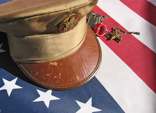 Military cap atop American flag