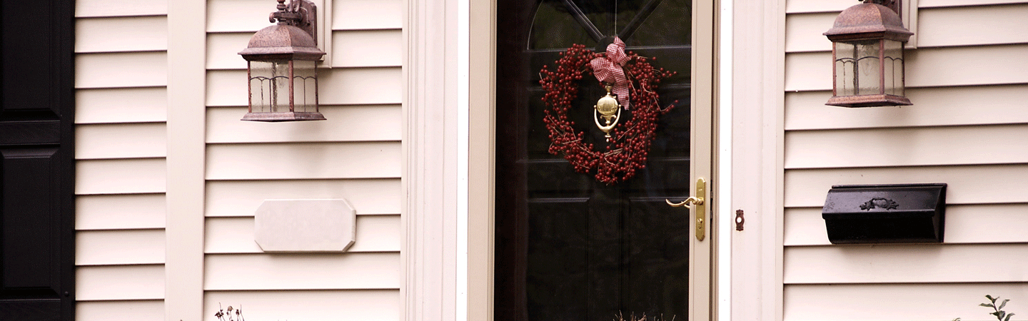Front door with mailbox and red wreath