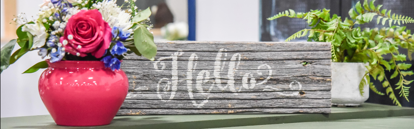Hello sign with vase of flowers