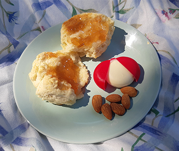 A plate with jam on a scone or biscuit, a few almonds and a small cheese.