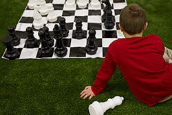 Kid playing with large chess pieces