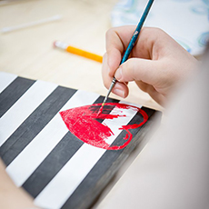 Painted heart on black and white striped canvas